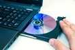 Man insert compact disc from laptop