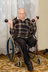 Senior disabled man exercising with dumbbells