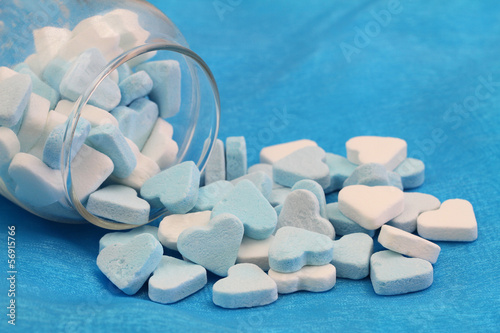Blue and white sugar hearts on blue background with copy space