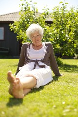 Old woman relaxing on grass