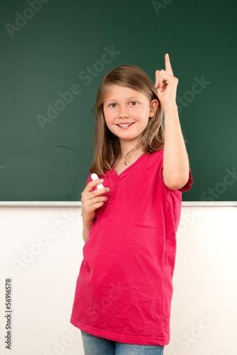 Schülerin steht vor einer Tafel