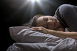 creepy glowing orb hovering over a woman sleeping in bed