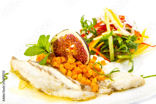 Baked fish with salad on a white background in restaurant