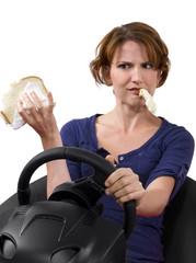 female driver eating a sandwich while driving