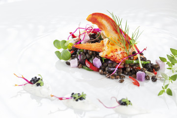 Lobster leg with black lentils salat and fresh sprouts