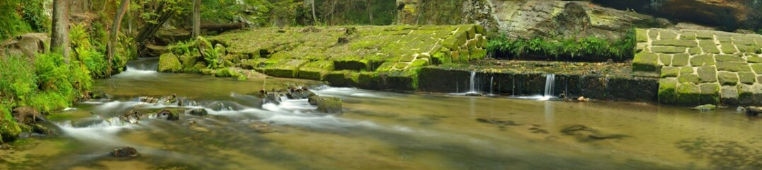 Ruins of sandstone weir on small mountain river