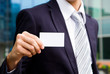 young businessman holding visit card in hand
