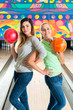 Young women playing bowling and having fun