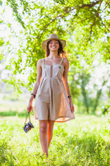 girl wearing straw hat walking with vintage camera