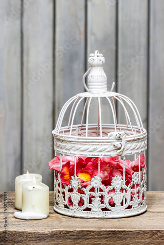 Birdcage with pink flowers inside on rustic wooden background