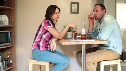 Unhappy, conflicted couple drinking wine at home
