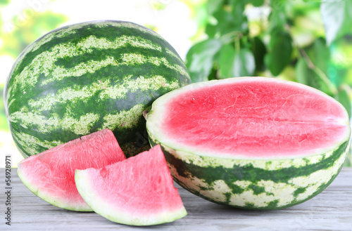 Ripe watermelons on wooden table on nature background