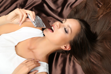 Woman lying on brown atlas with chocolate