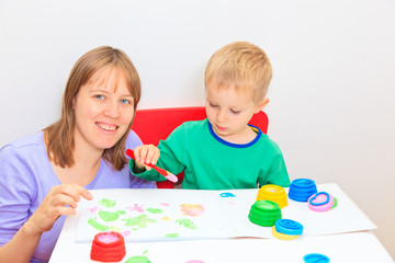 Child with teacher drawing in playroom
