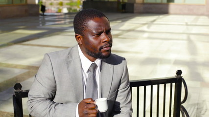 businessman sitting on the bench and drinking coffee