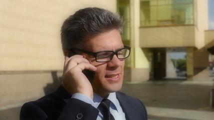 Tilt down of a mature businessman calling