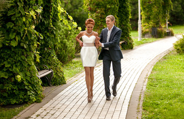 Beautiful girl in white dress walking in park with boyfriend