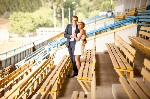 Newly married couple posing on stadium