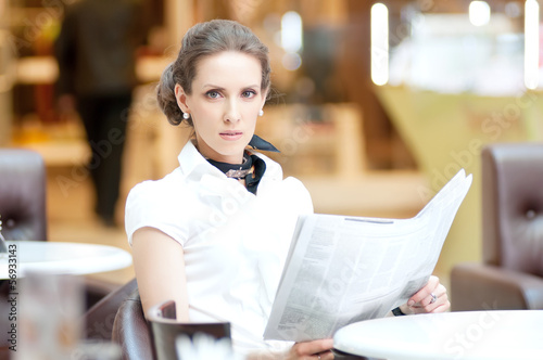 Serious business woman reading newspaper