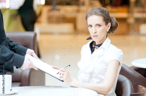 Businesswoman writing with pen: sign document