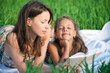 Happy girls reading book on green grass