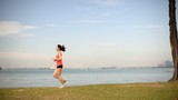 Asian Chinese lady jogging by the sea across the frame