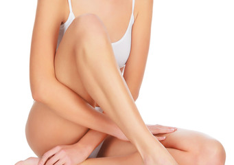 Woman touches her leg, white background, copyspace.