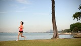Asian Chinese lady jogging by the sea