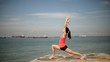 Panning shot of Asian lady doing yoga by the sea