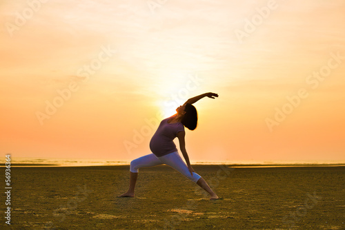 pregnant mother performing yoga on outdoor beach