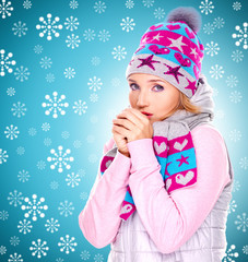 beautiful woman in winter clothes warming her hands