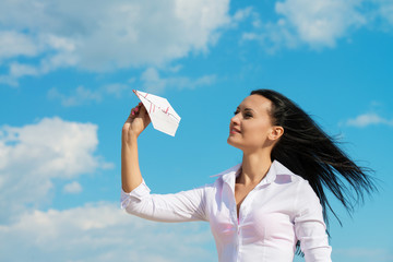 Young office lady with paper plane, outdoors portrait