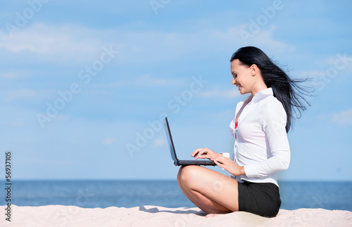 Portrait of office lady with laptop at the beach