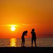 Silhouetten von Kindern die bei Sonnenuntergang angeln
