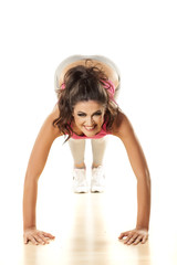 Front view of a pretty smiling girl doing push-ups on white