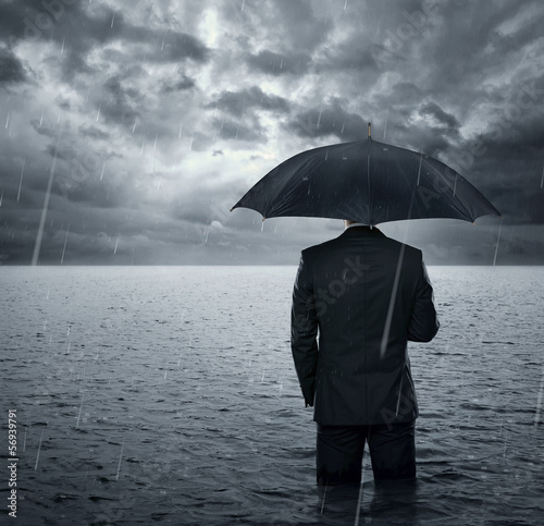 Businessman standing in the dramatic ocean before storm