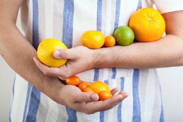 man hands holding citrus fruits
