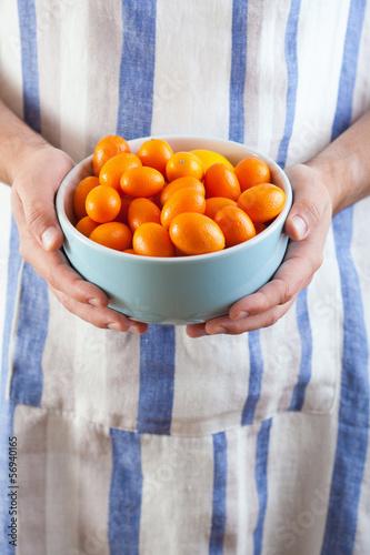 man hands holding bowl of kumquat
