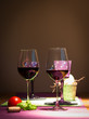 two redwine glasses with tomato and basil on table for couple