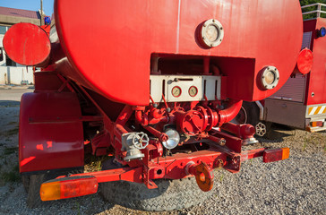 The rear of red fire truck with water pump equipment