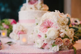 Wedding bouquet of roses in front of wedding cake.