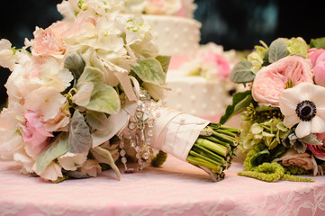 Roses bouquet wrapped in ribbon in front of wedding cake.