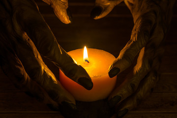 Candlelight illuminating the werewolf hands close-up