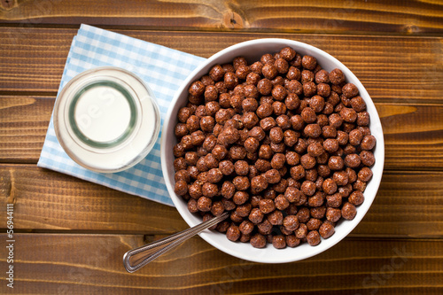 chocolate cereals in bowl and milk in jar