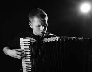 musician plays the accordion against a dark background