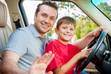 Father and son is sitting at the stearing wheel and smiling at t