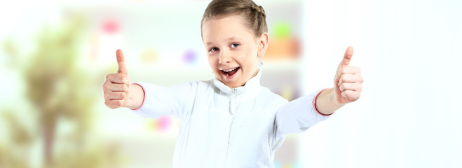 Little girl showing the thumbs up isolated on background