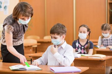 school kids and teacher with protection mask against flu virus a
