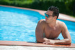 Portrait of a handsome man relaxing by swimming pool.