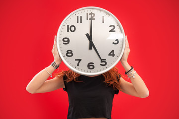 Young woman holding office clock against red background.